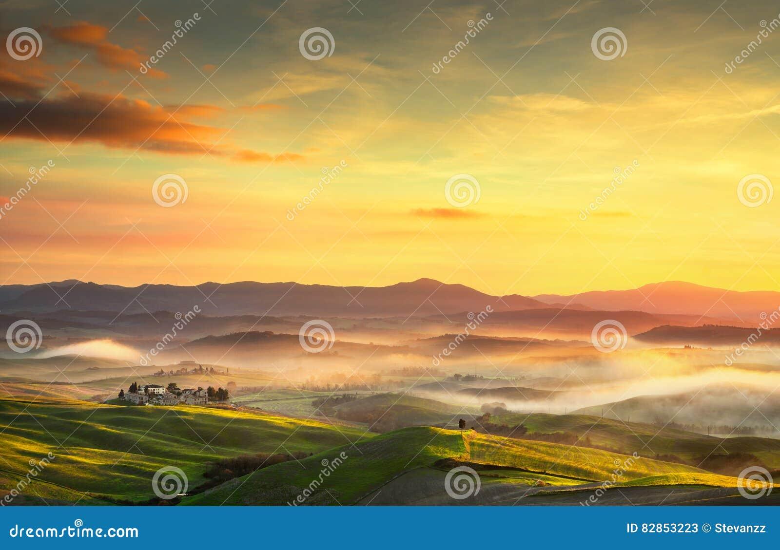 Panorama nebbioso di Volterra, Rolling Hills e campi verdi su sunse