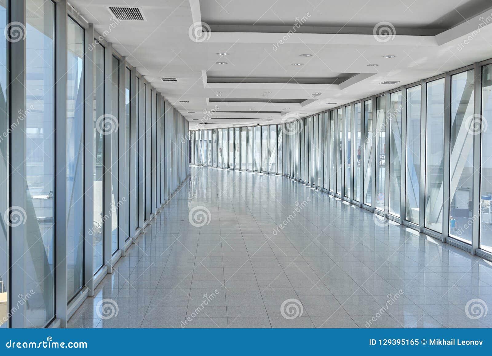 Panorama op lege bureauzaal met de vensters van de glasmuur gemaakt van metaal en glas Moderne gangmetaal en glasbouw