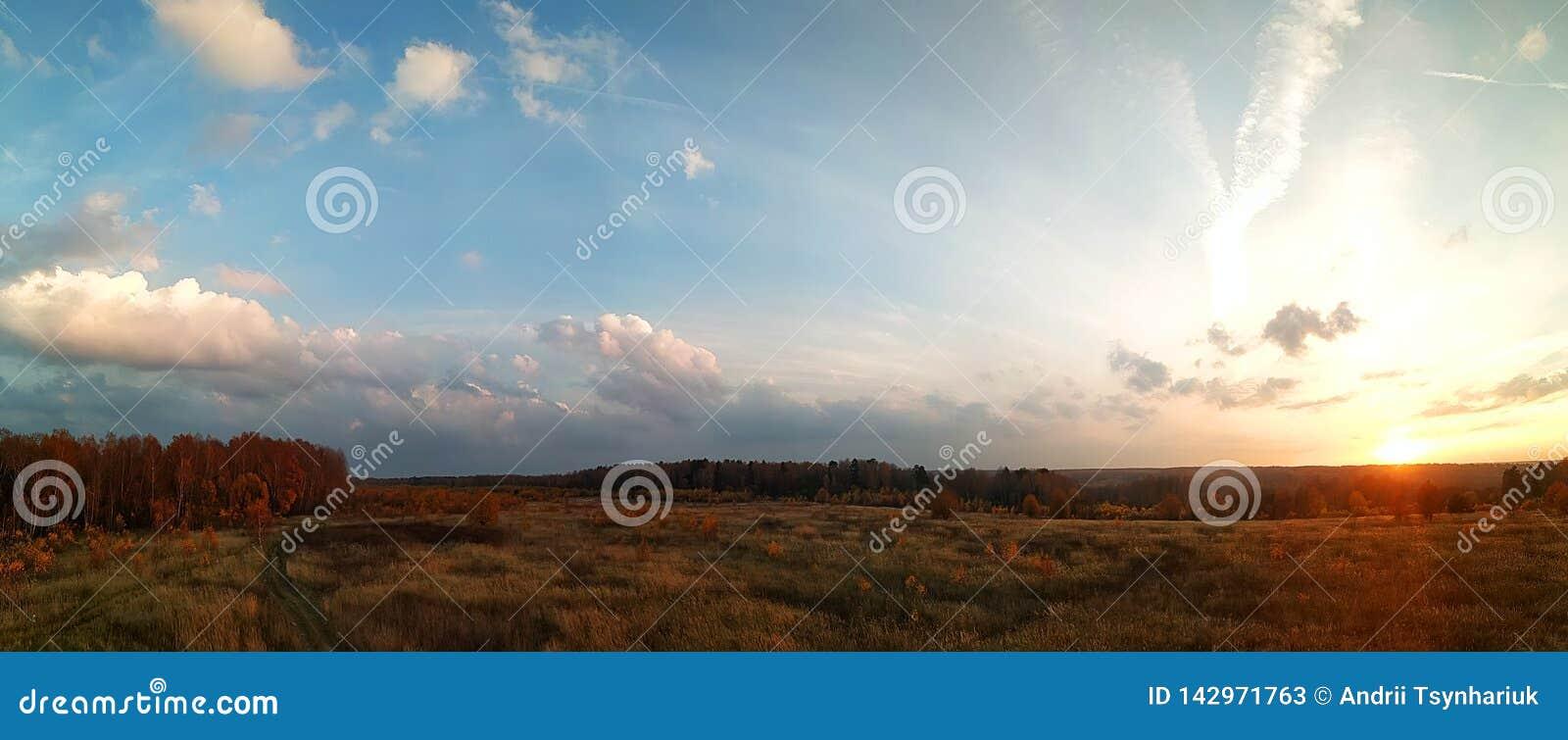 Panorama que sorprende del paisaje rural del otoño de un pueblo europeo con un cielo colorido y un campo de oro infinito