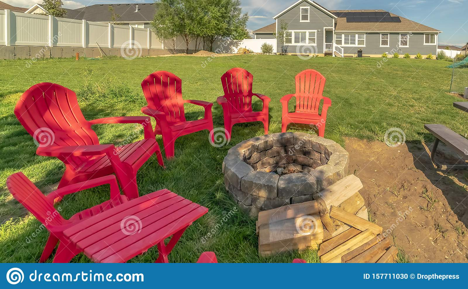 Panorama Red Outdoor Chairs And Picnic Table With Bench Around A Circular Stone Fire Pit Stock Photo Image Of Grass Seat 157711030