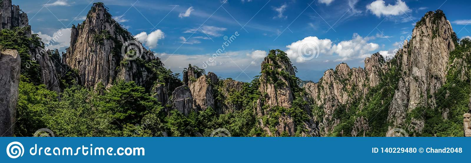 Panorama of rocky peaks and old pine trees cover the mountains under a bright blue sky with whispy clouds in Huangshan China