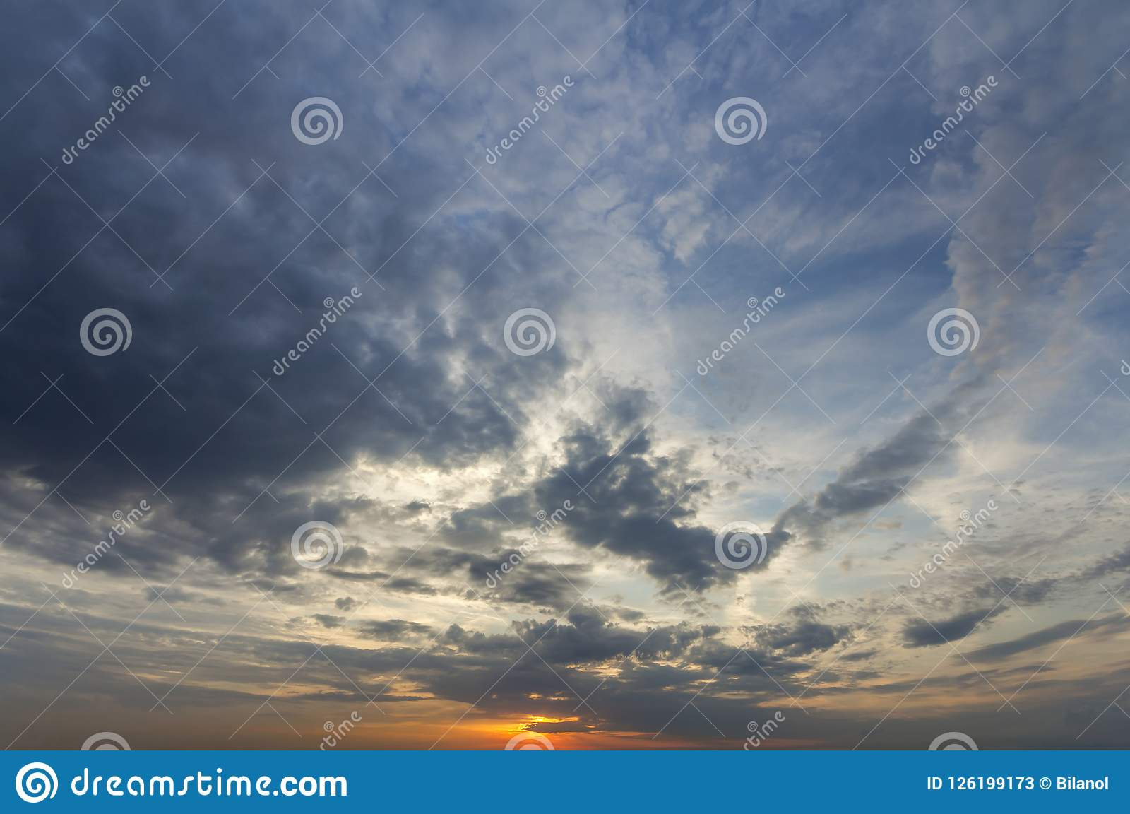 Panorama of sky at sunrise or sunset. Beautiful view of dark blue clouds lit by bright orange yellow sun on clear sky. Beauty and
