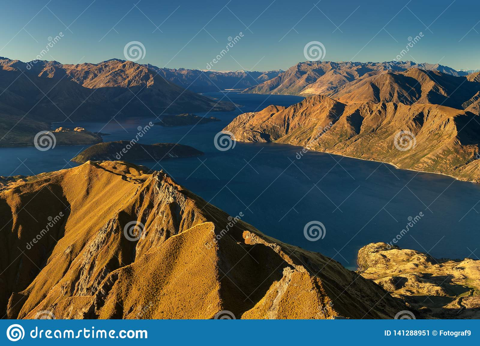 Panorama at sunset of Roys Peak between Wanaka and Queenstown with a lake and Mount Aspiring and cook of the new zealand alps.