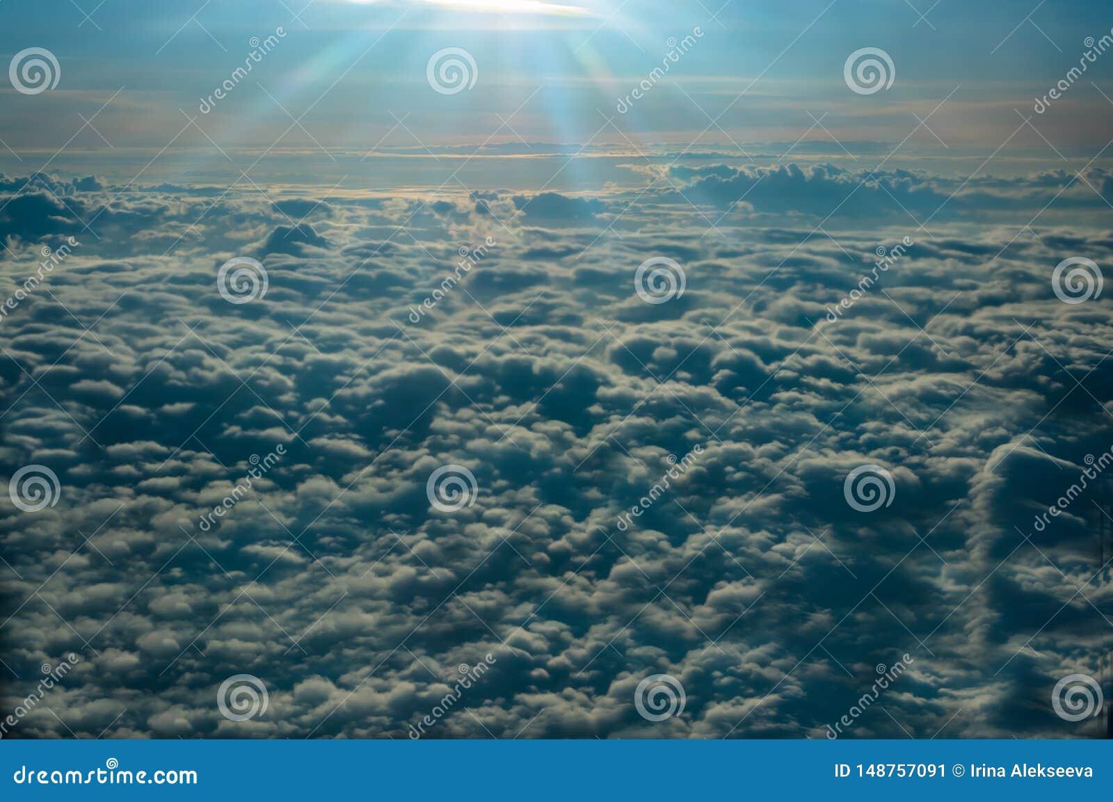 Panorama van het venster van het vliegtuig die boven de zonovergoten wolken vliegen
