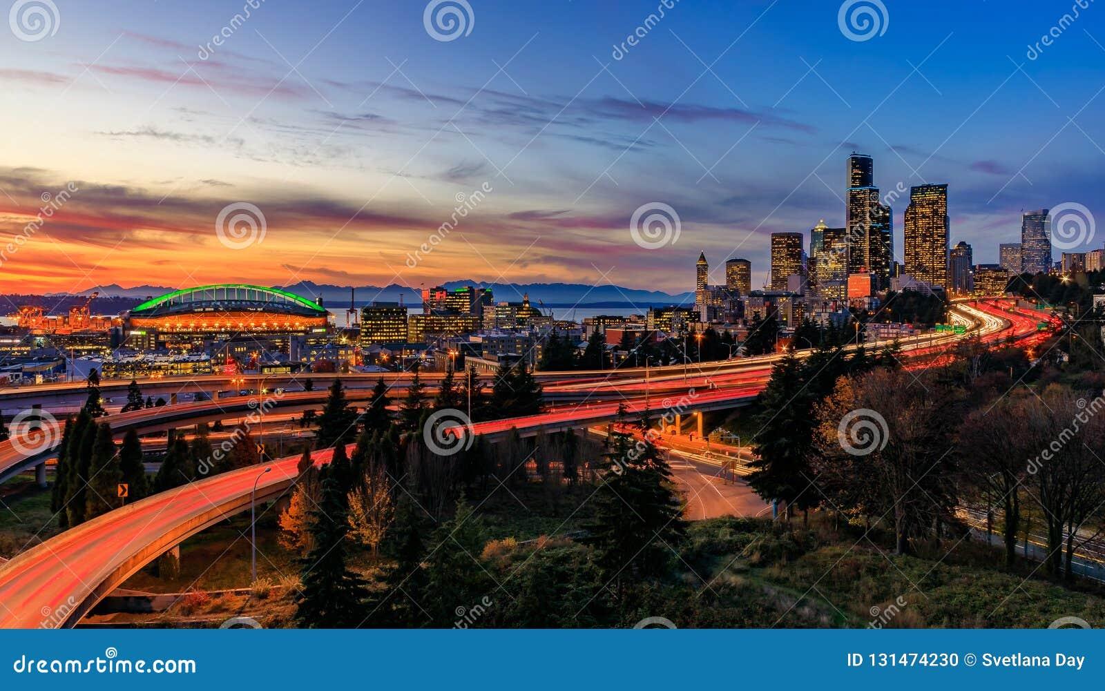 Panorama von im Stadtzentrum gelegenen Skylinen Seattles über dem I-5 I-90 Autobahnaustausch bei Sonnenuntergang mit langen Belic