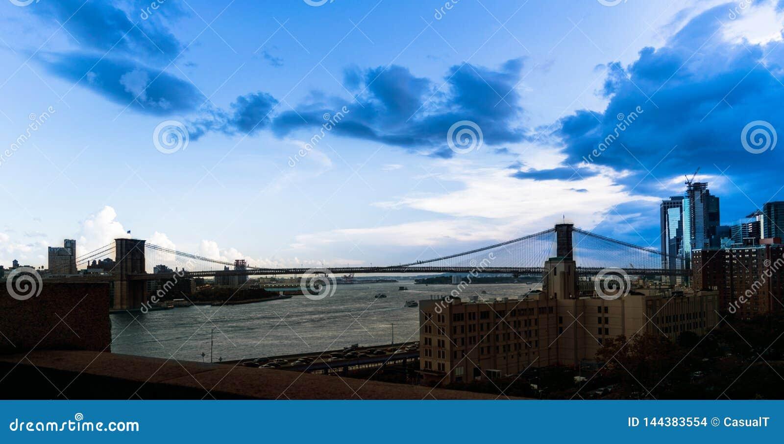 Panoramablick der Brooklyn-Brücke, die den East River, unter einem beträchtlichen blauen Frühabend-Himmel im Stadtzentrum überspa