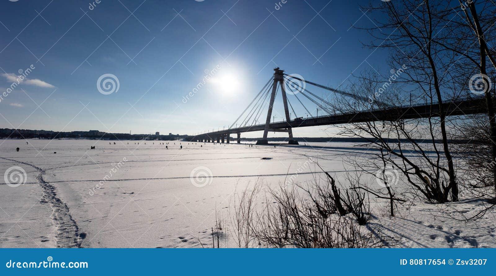 Panoramablick der Kabel-gebliebenen Rohrleitung in Chrepovetz, Russland am sonnigen Tag des Winters Gruppenskifahrer und -fischer