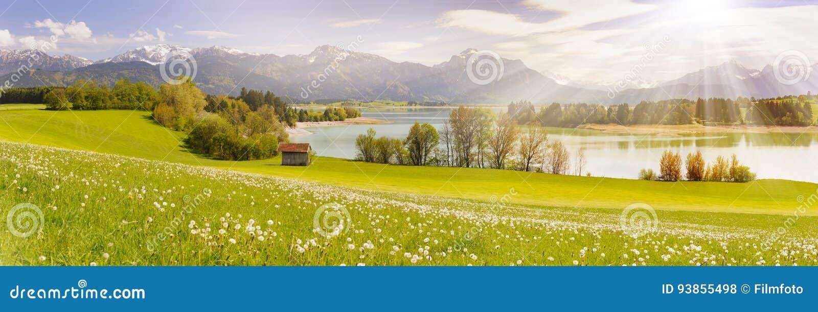 Panoramaszene im Bayern, Deutschland an den Alpenbergen mit Sonnenstrahlen über See