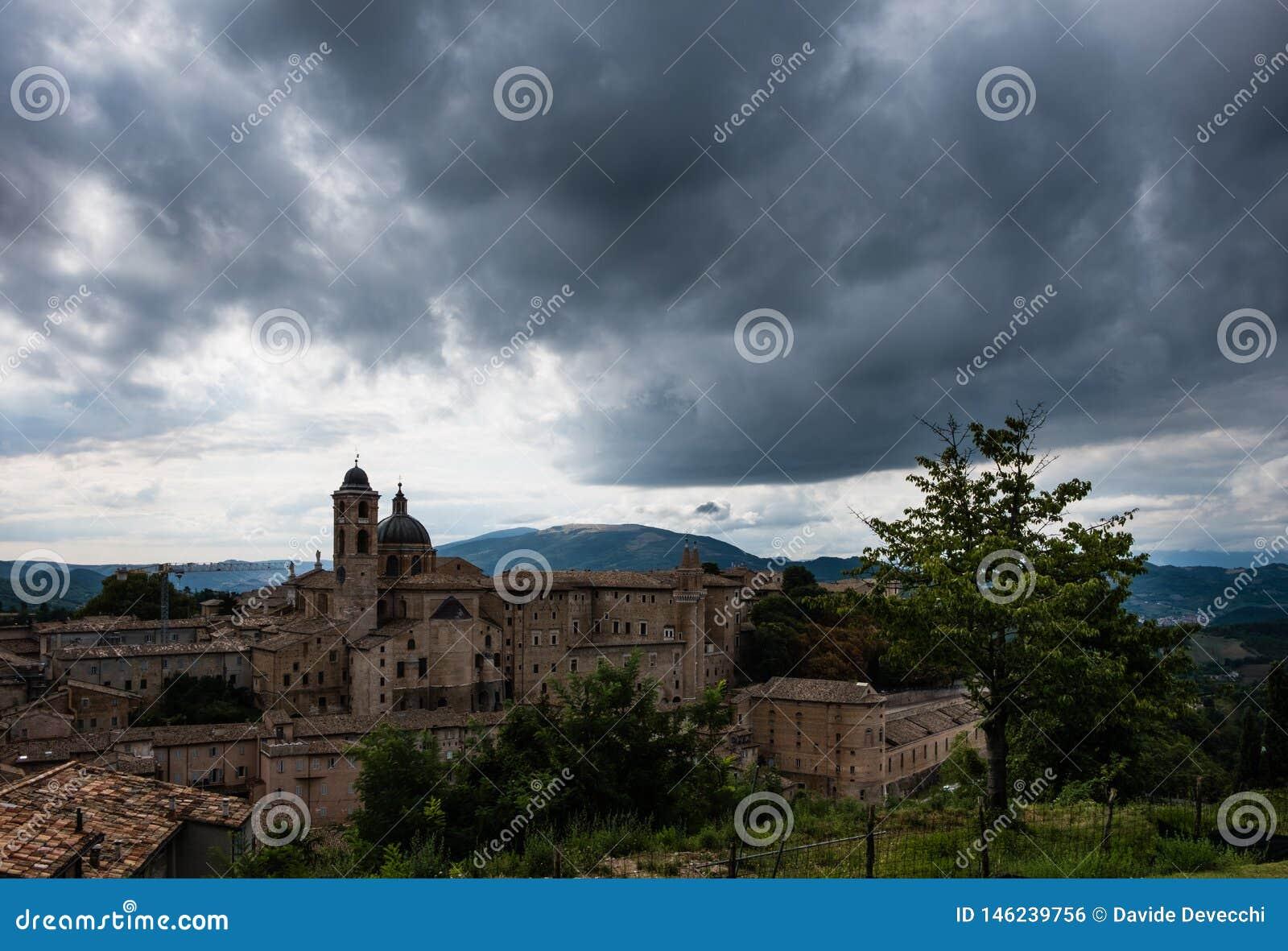 Panoramautsikt av den hertigliga slotten av Urbino i centrala Italien med en dramatisk himmel