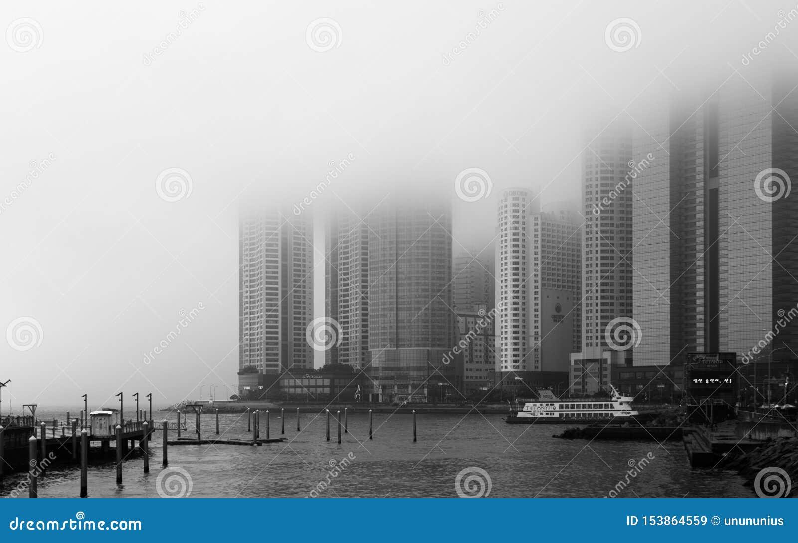 Panoramautsikt av kustlinjen, hamnfjärd med promenad och skyskrapor av Hanwha Resort Haeundae på en dimmig dag Haeundae-gu