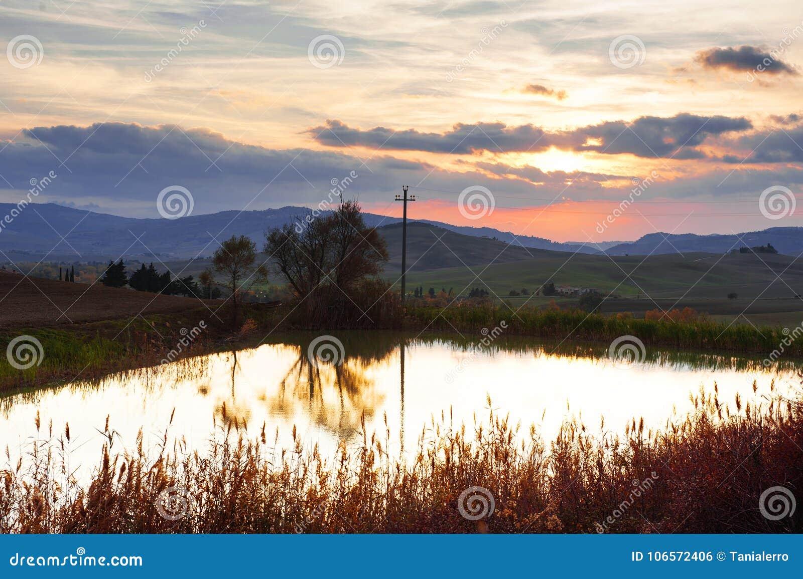 Panoramautsikt av lite dammet, Rolling Hills, himmel och moln på solnedgången i tuscan bygdlandskap, Tuscany, Italien