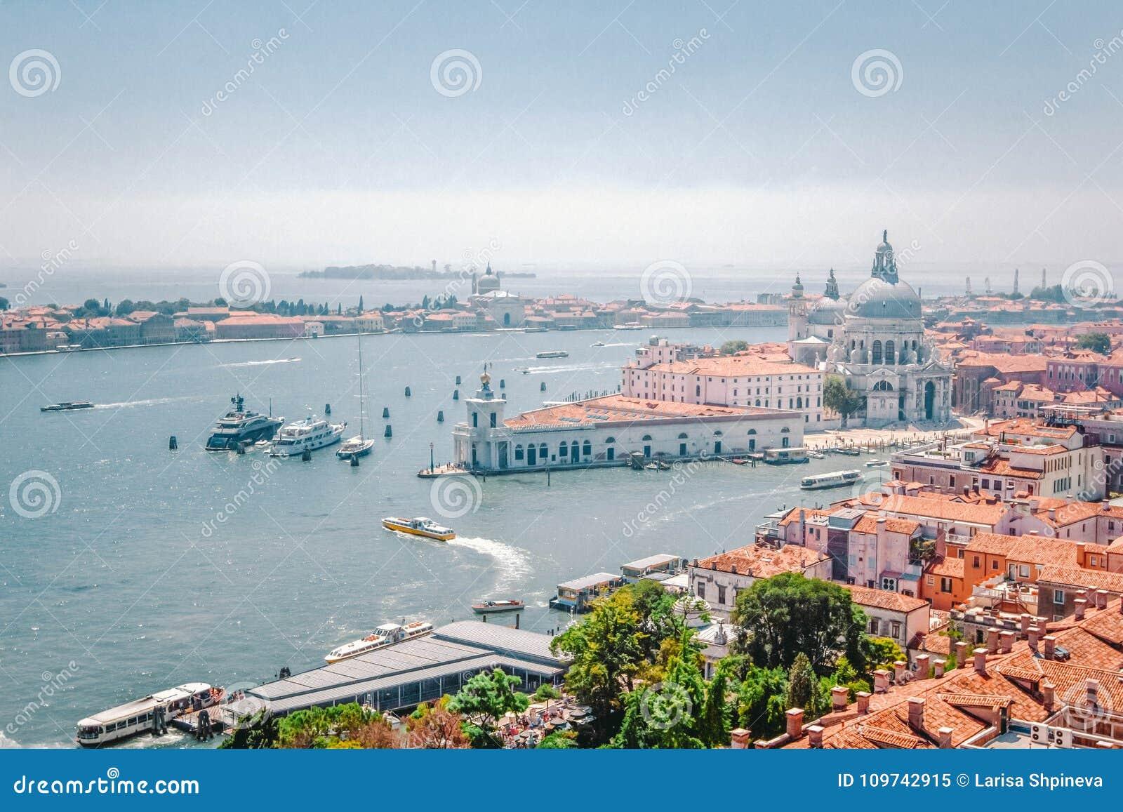 Panoramautsikt av Venedig - Grand Canal med gondoler, basilikan Santa Maria della Salute och röda belade med tegel tak av hus, Ve