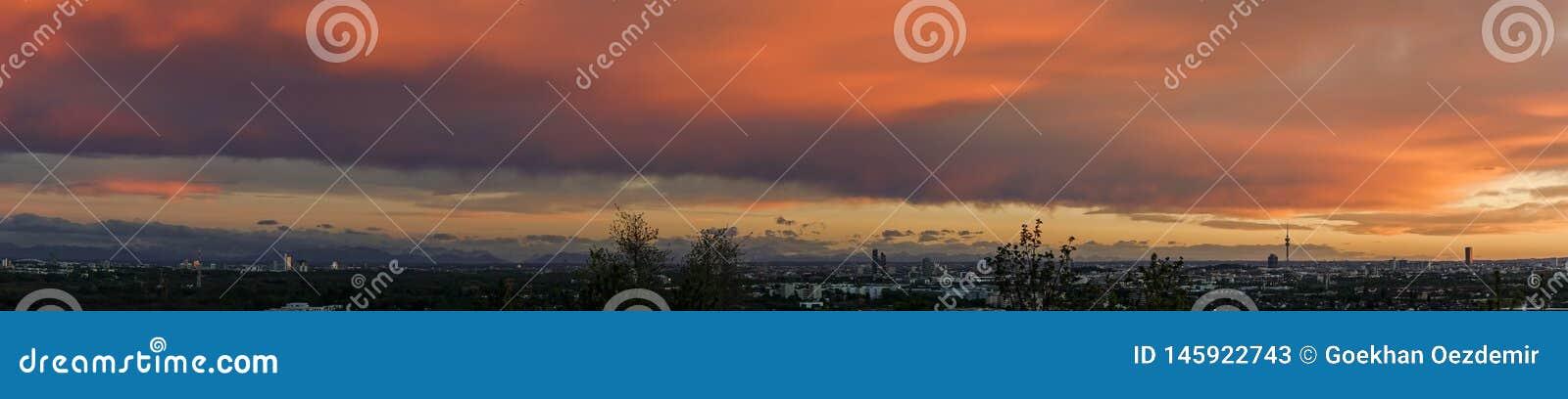 Panoramautsikt som tas på solnedgången över den munich staden i bavaria, Tyskland med dramatiska molnig himmel och berg i bakgrun