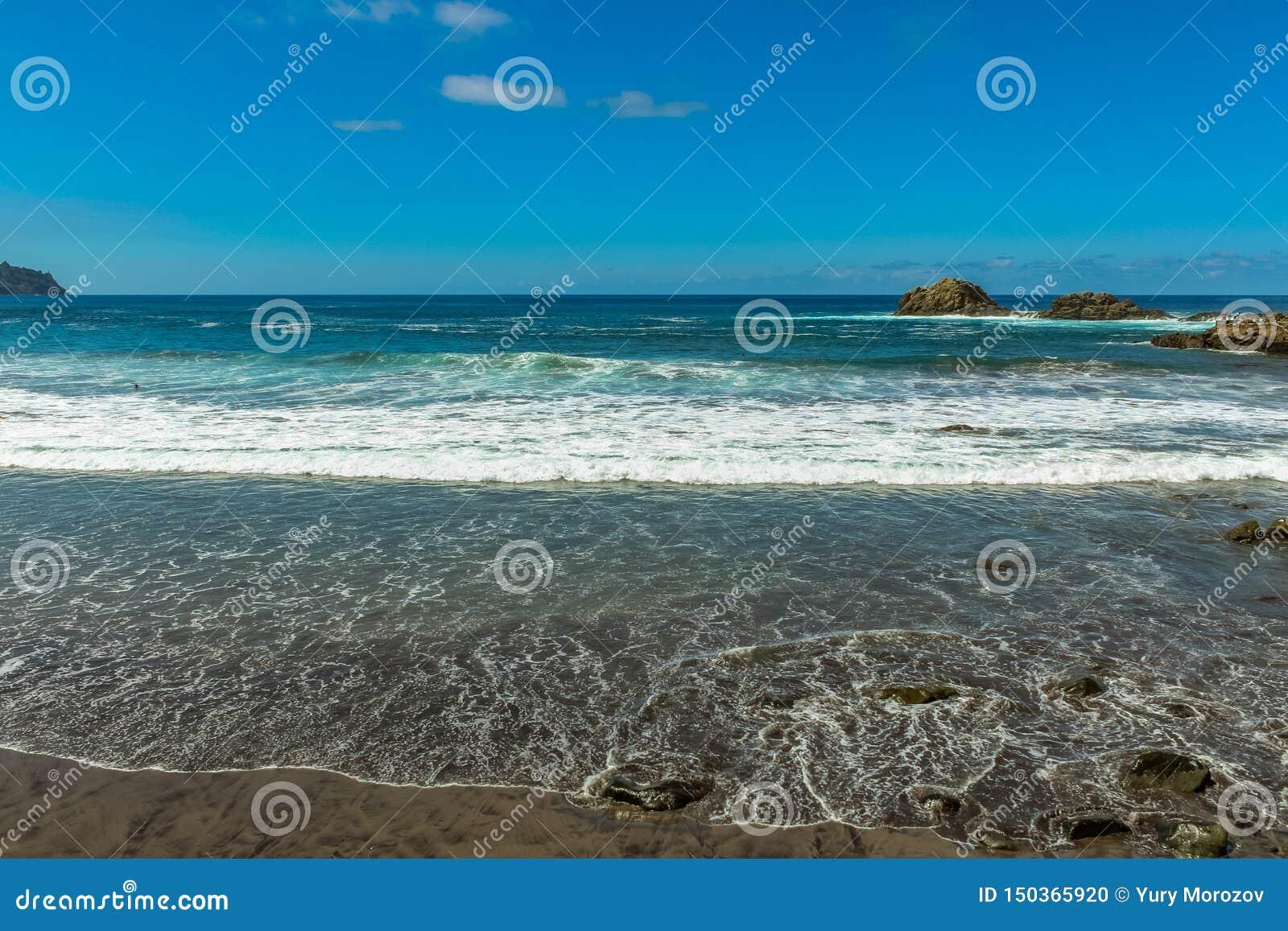Panoramautsikten av den Aimasiga stranden med vulkanisk svart sand och ensamt vaggar att klibba ut ur havsskumet på norrkusten av
