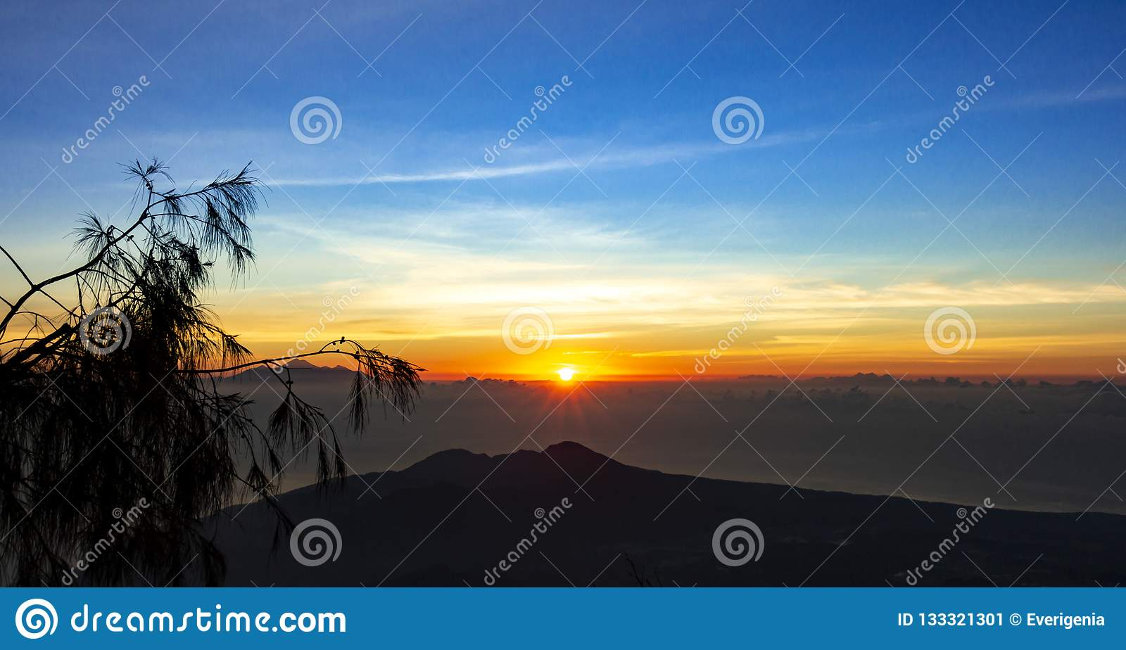 Panoramic beautiful view from top of the volcano Agung at dawn. View of the rising sun and Rinjani mount on the horizon from a