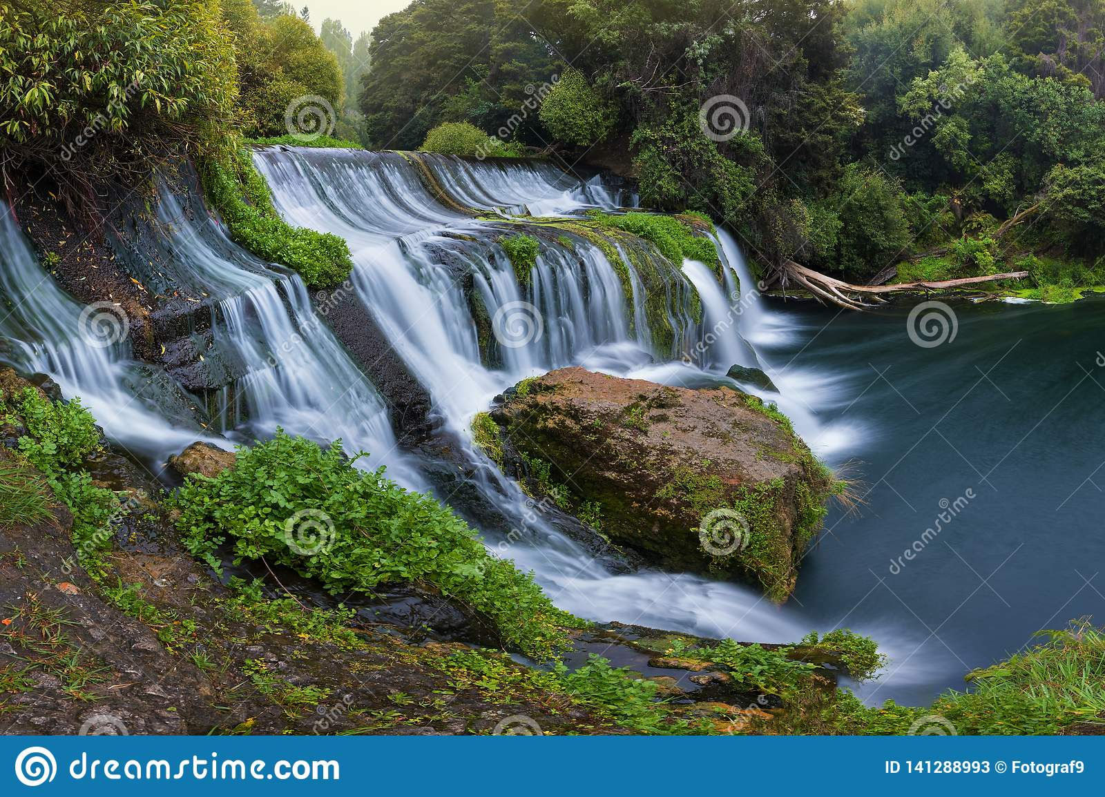 Panoramic photo landscape / Waterfall hidden in the tropical jungle surrounded by a natural swimming pool with clear fresh water.
