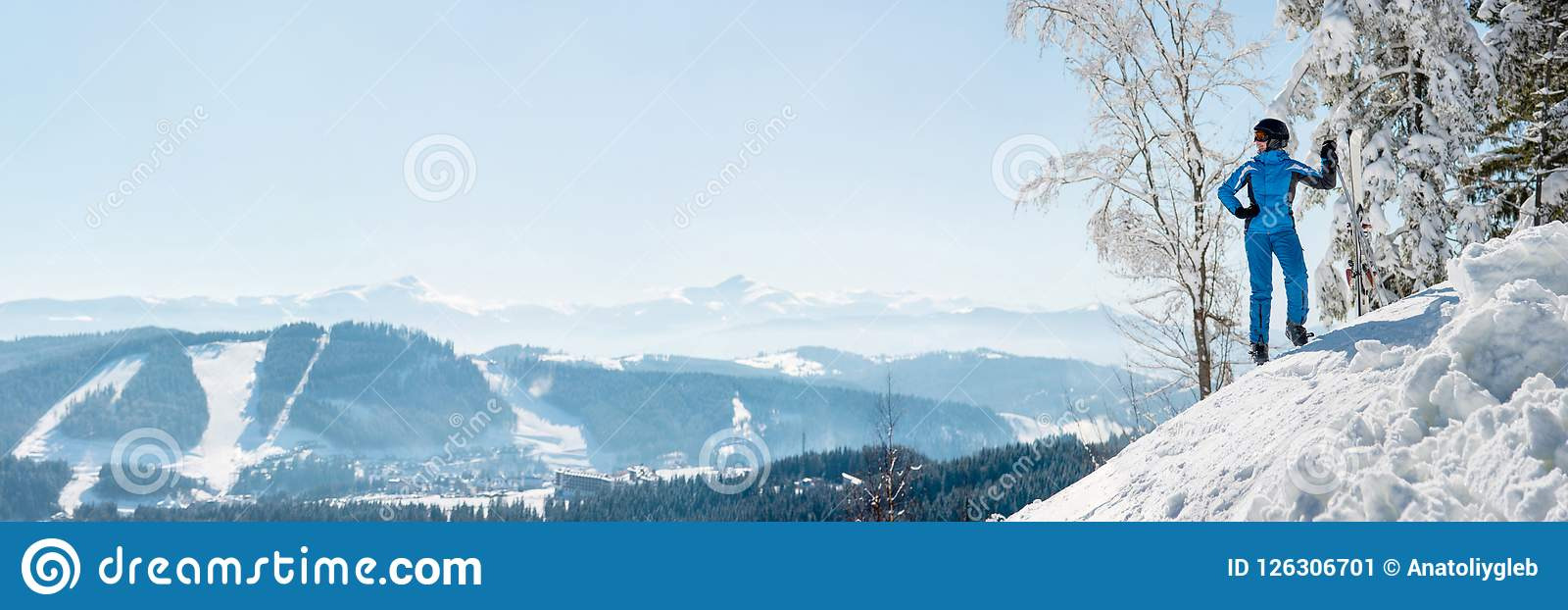 Panoramic shot of a female skier resting on top of the mountain observing nature at ski resort