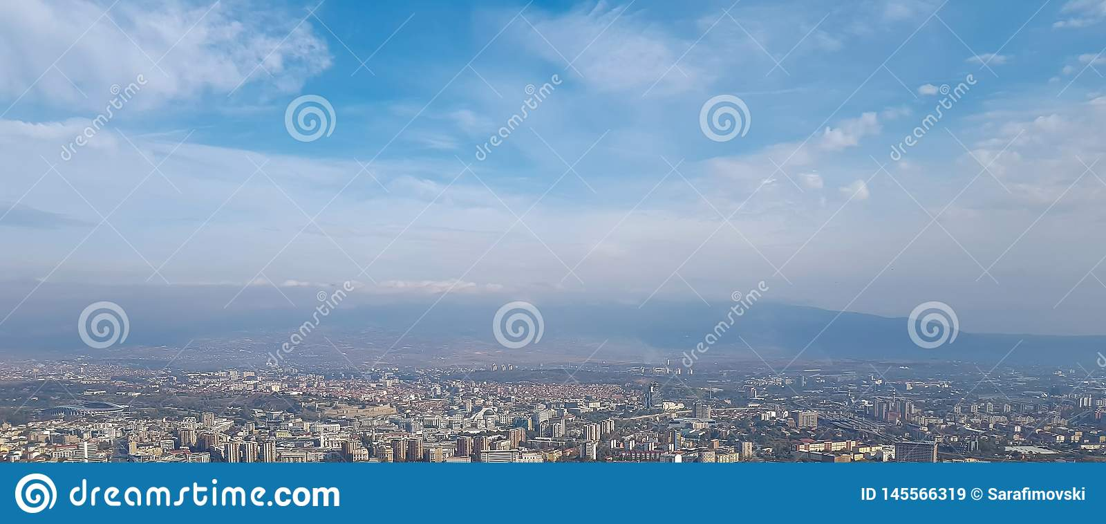 Panoramic skyline and buildings with blue sky and white clouds.