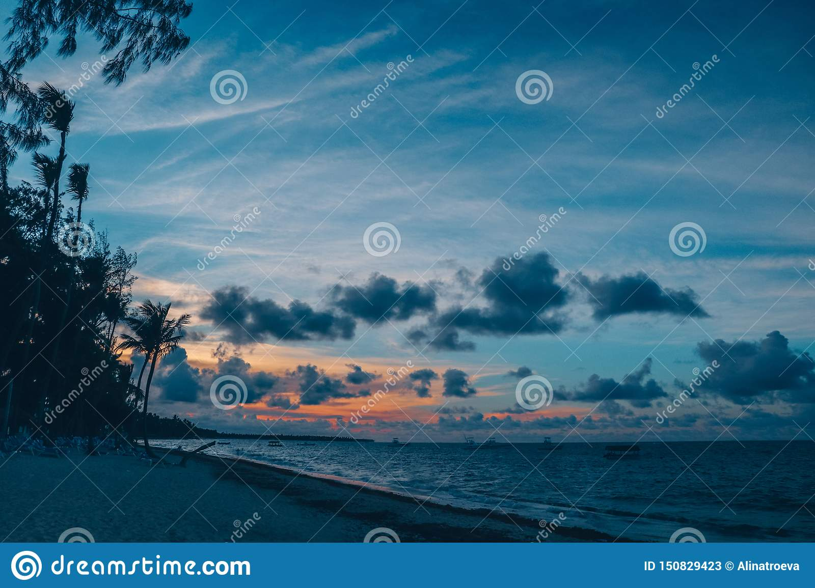 Panoramic sunset view of the tropical beach, ocean, and blue sky