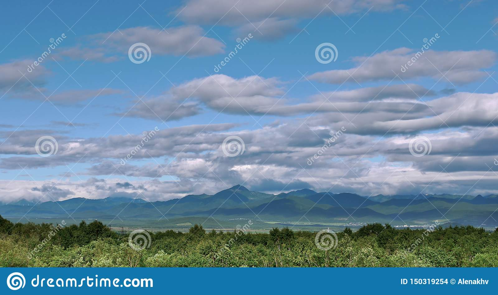 Panoramic view of beautiful clouds over a green hill valley