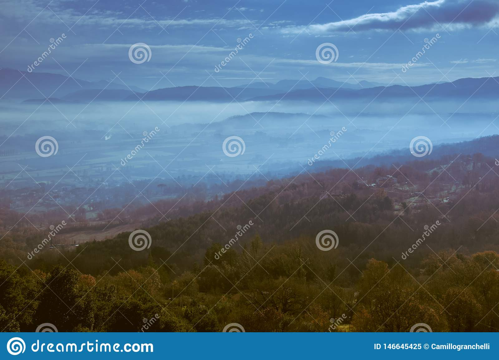 Panoramic view from a hill in the evening with low clouds over the valley