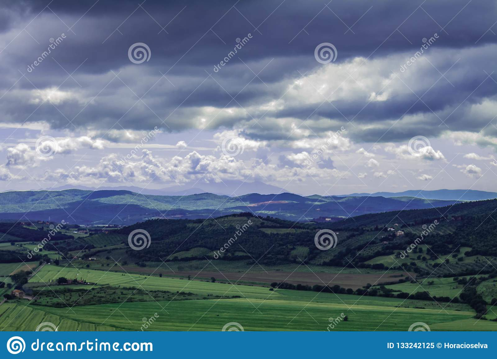 Panoramic view of the italian tuscany. The mountains in the distance are covered by clouds