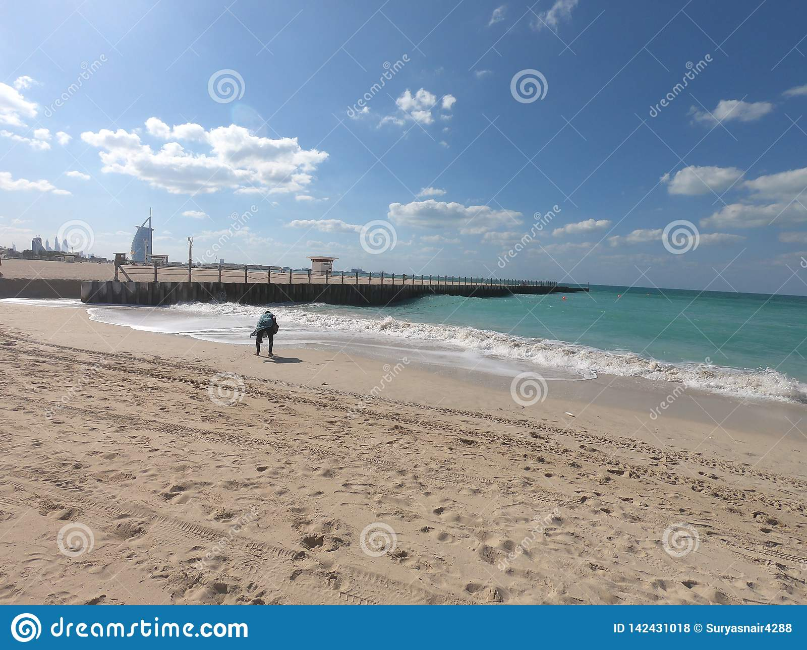 Panoramic View of Jumeirah Beach and Burj Al Arab and View of Pier. Woman picking up Shells at beach