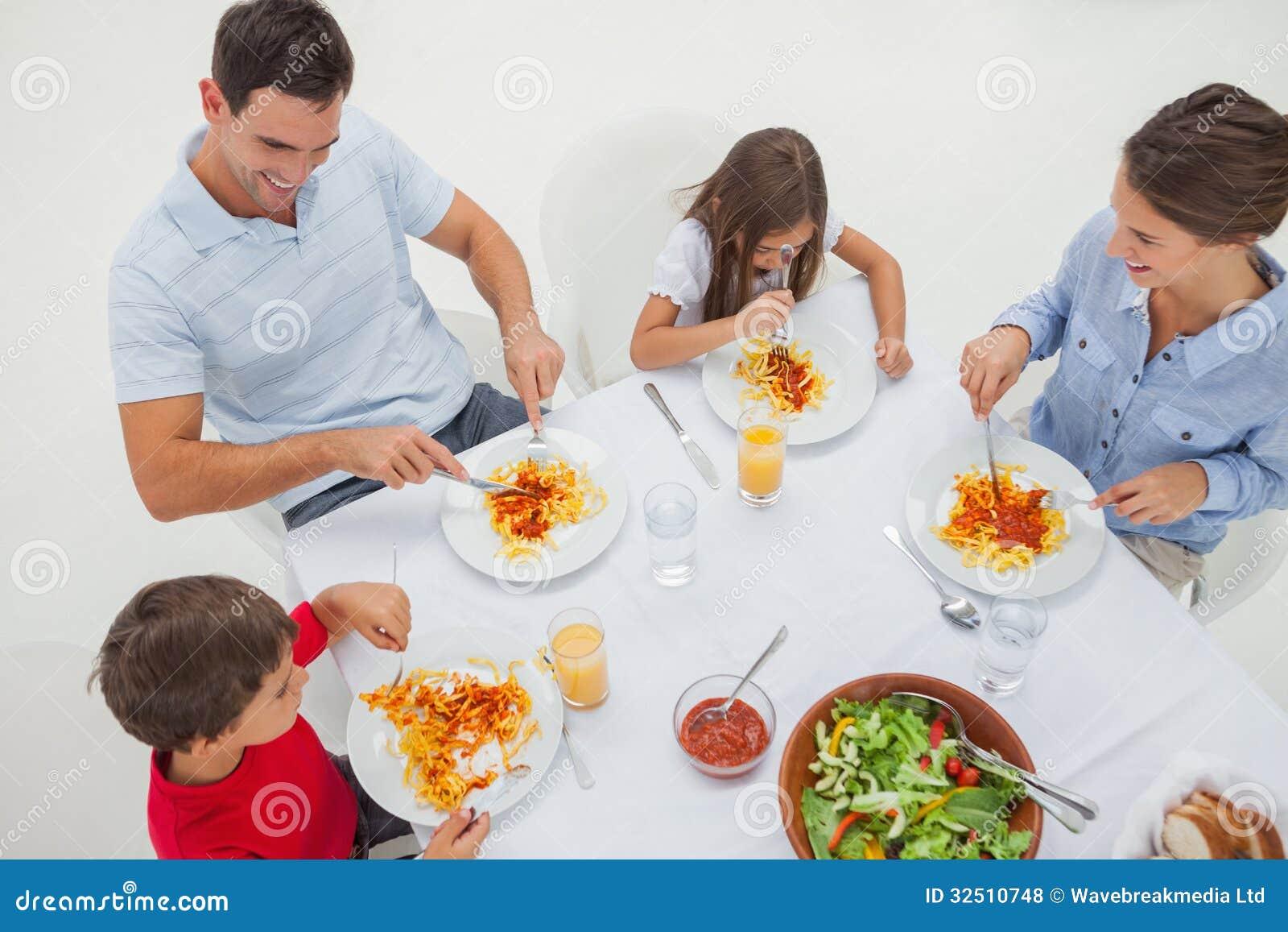 Panoramica di una famiglia che mangia pasta con salsa ed insalata