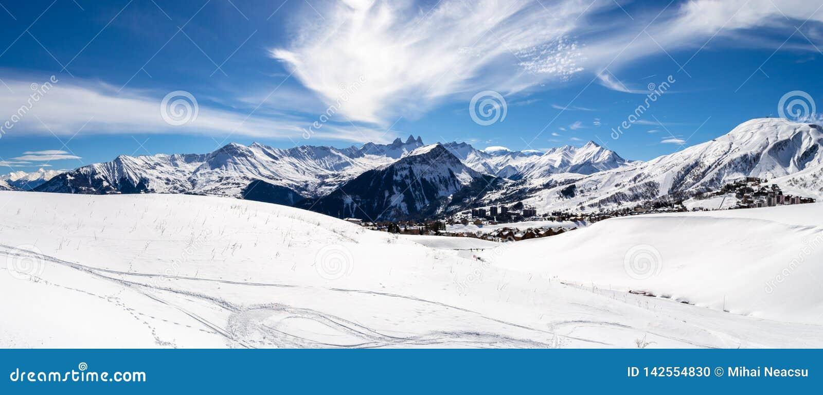 Panoramiczny krajobraz z halnymi szczytami w Francuskich Alps nad losu angeles Toussuire wioska na pogodnym zima dniu w Les Sybel