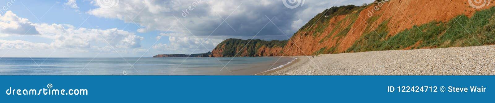Panoramiczny widok falezy przy Sidmouth w Devon, pokazywać kamiennego brzeg i utleniać falezy w zatoce