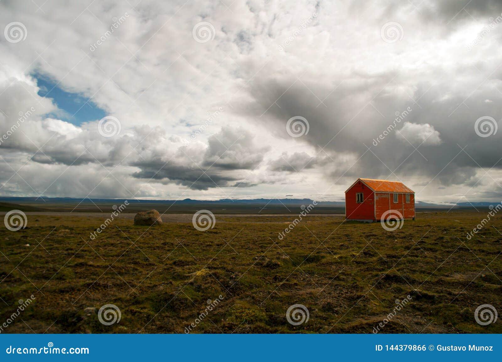 Panoramisch van het oude rode buitenhuis op het centrale gebied van IJsland op een bewolkte dag