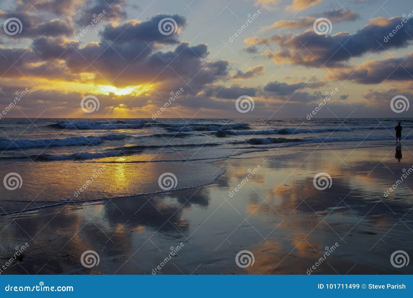Panoramische Szene des Ozeansonnenuntergangs mit Wolken dachte über nassen die watende Strand und Person nach