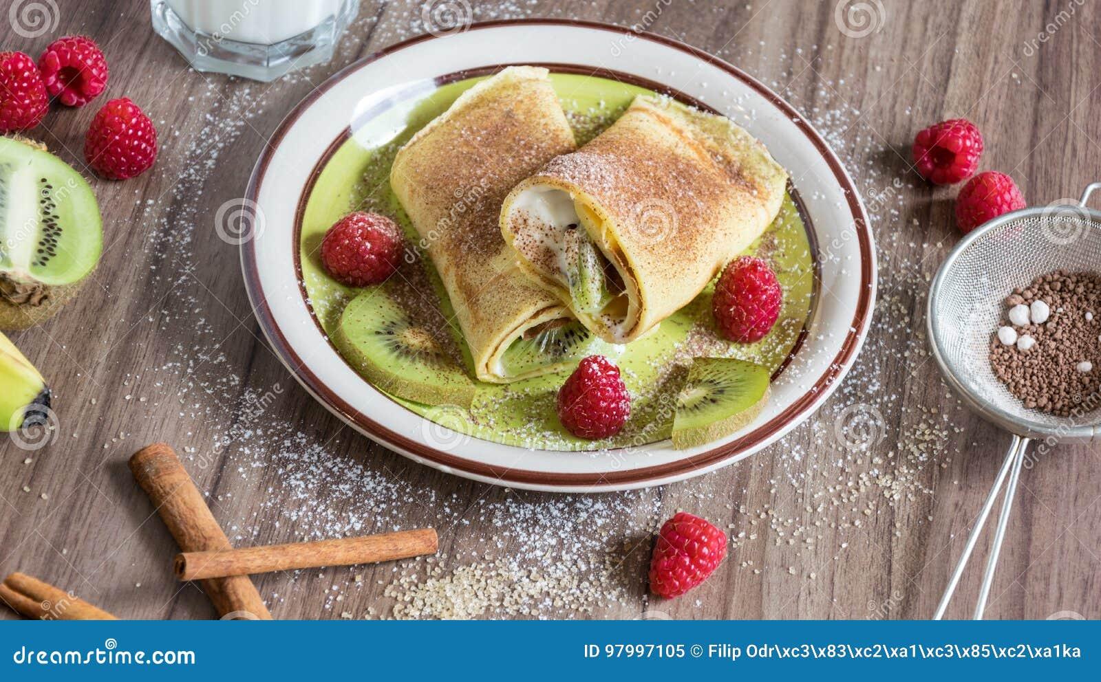Panqueca caseiro com as partes do coalho, das framboesas, do quivi e da banana da baunilha polvilhadas com o cacau
