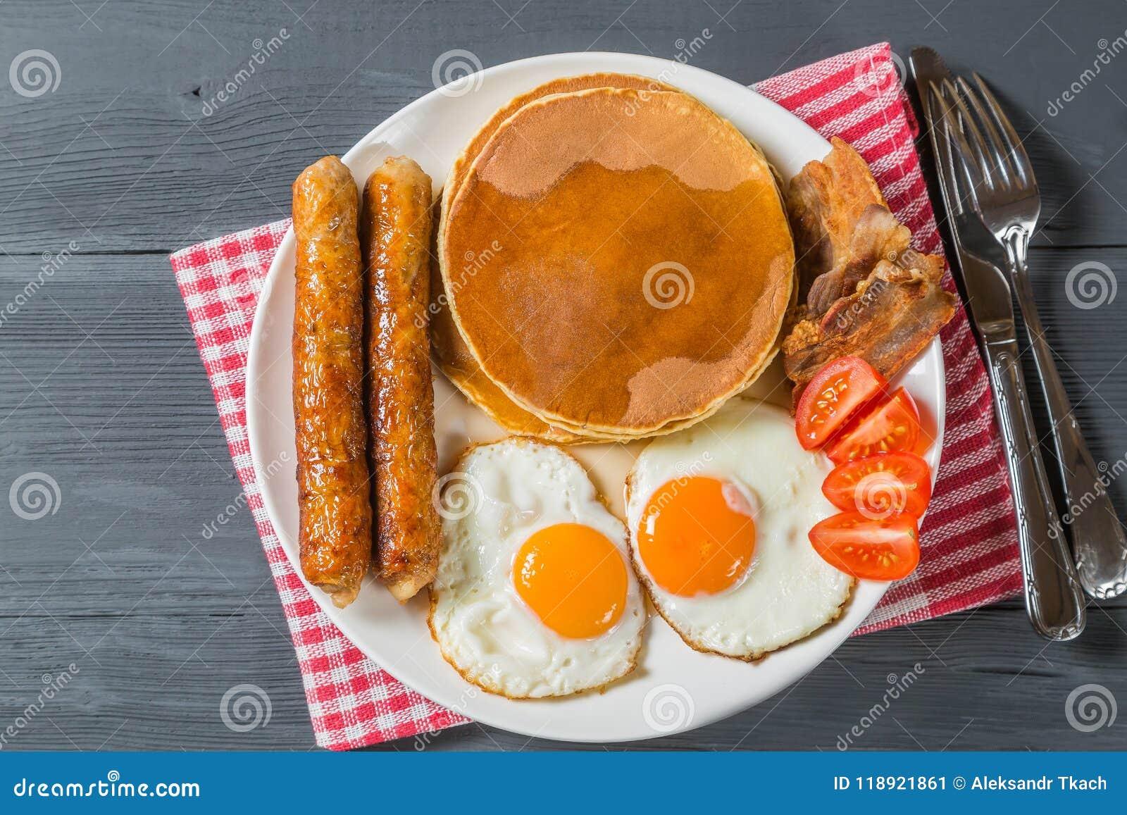 Panqueca com xarope do ovo, da salsicha, do bacon e de bordo A vista da parte superior Cópia-espaço