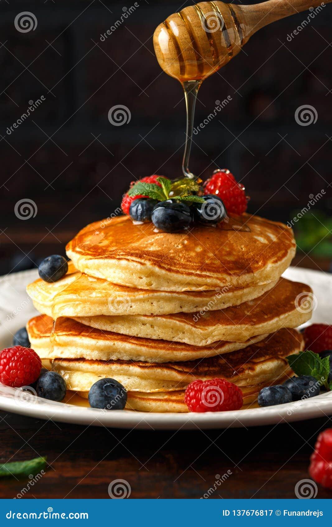 Panquecas americanas caseiros com mirtilo, as framboesas e mel frescos Estilo rústico do café da manhã saudável da manhã