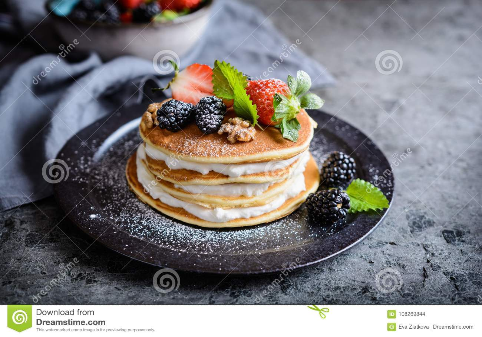 Panquecas americanas com chantiliy, morangos, amoras-pretas, nozes e açúcar pulverizado