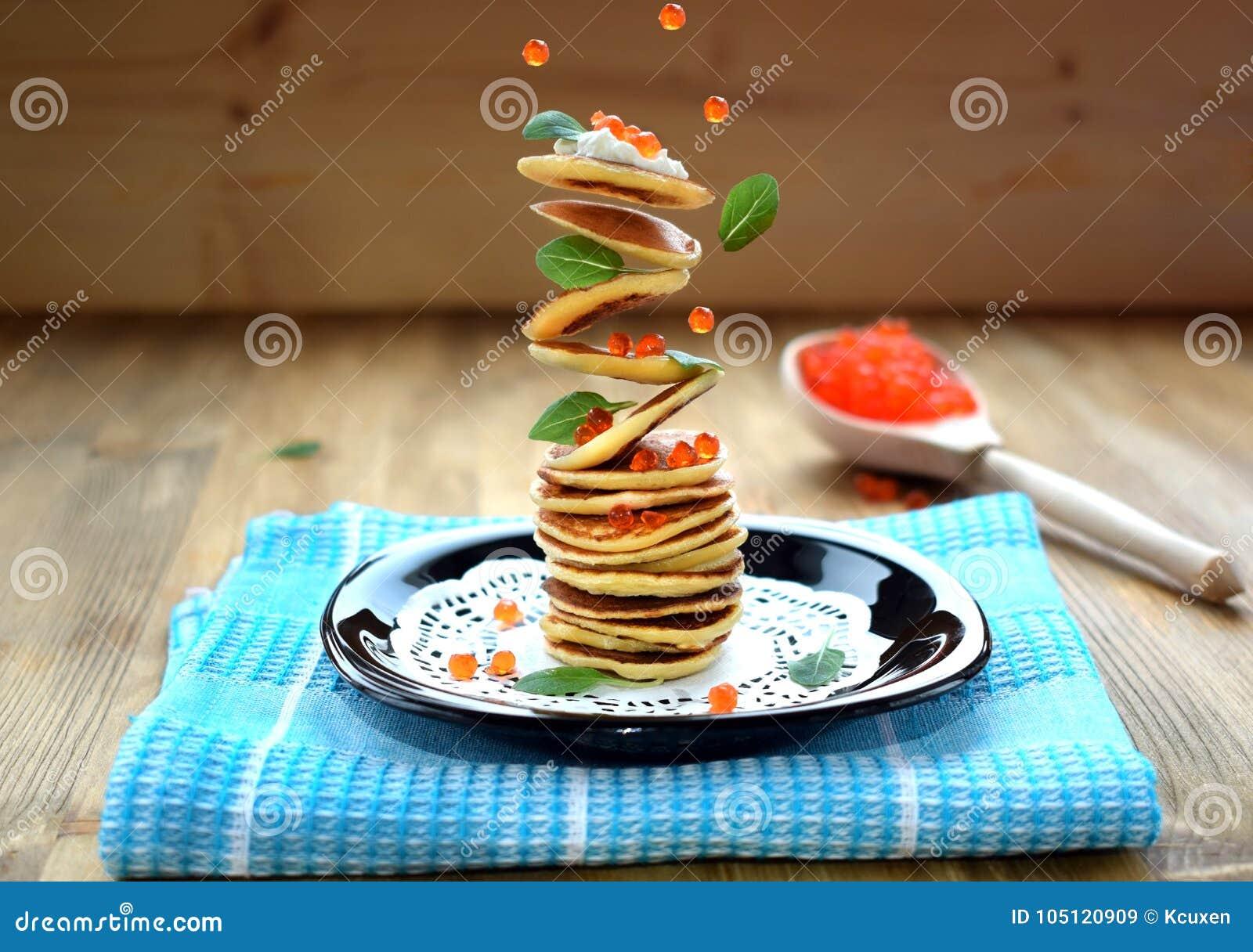 Panquecas de voo, caviar vermelho e folhas da manjericão Levitando o alimento