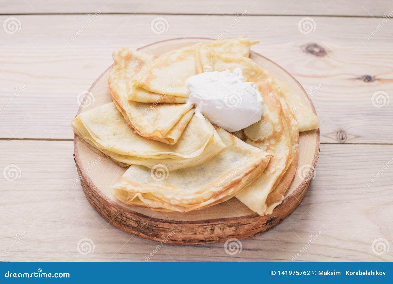 Panquecas finas do russo em um suporte de madeira feito da madeira natural com creme de leite Maslenitsa é um festival do aliment