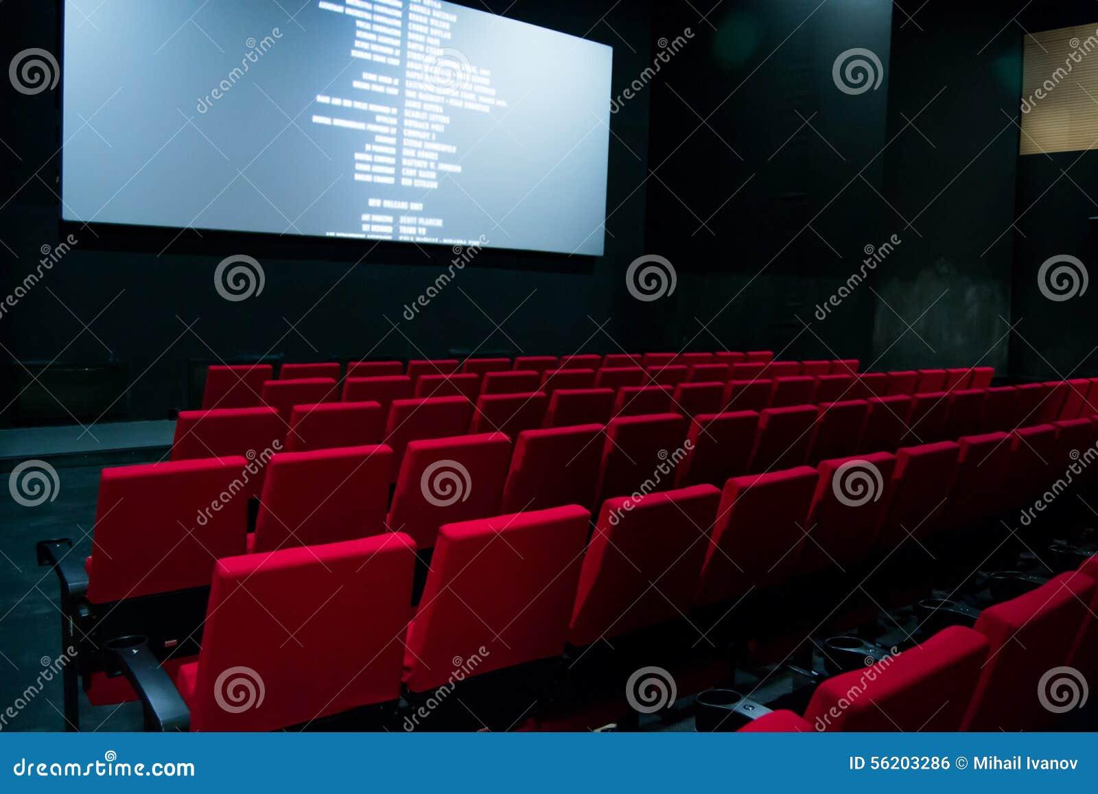 Pantalla de cine y sillas rojas dentro de un cine