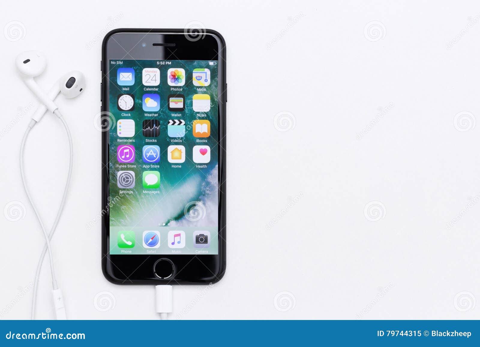 Pantalla de IPhone 7 que muestra el uso y earpods en la tabla blanca