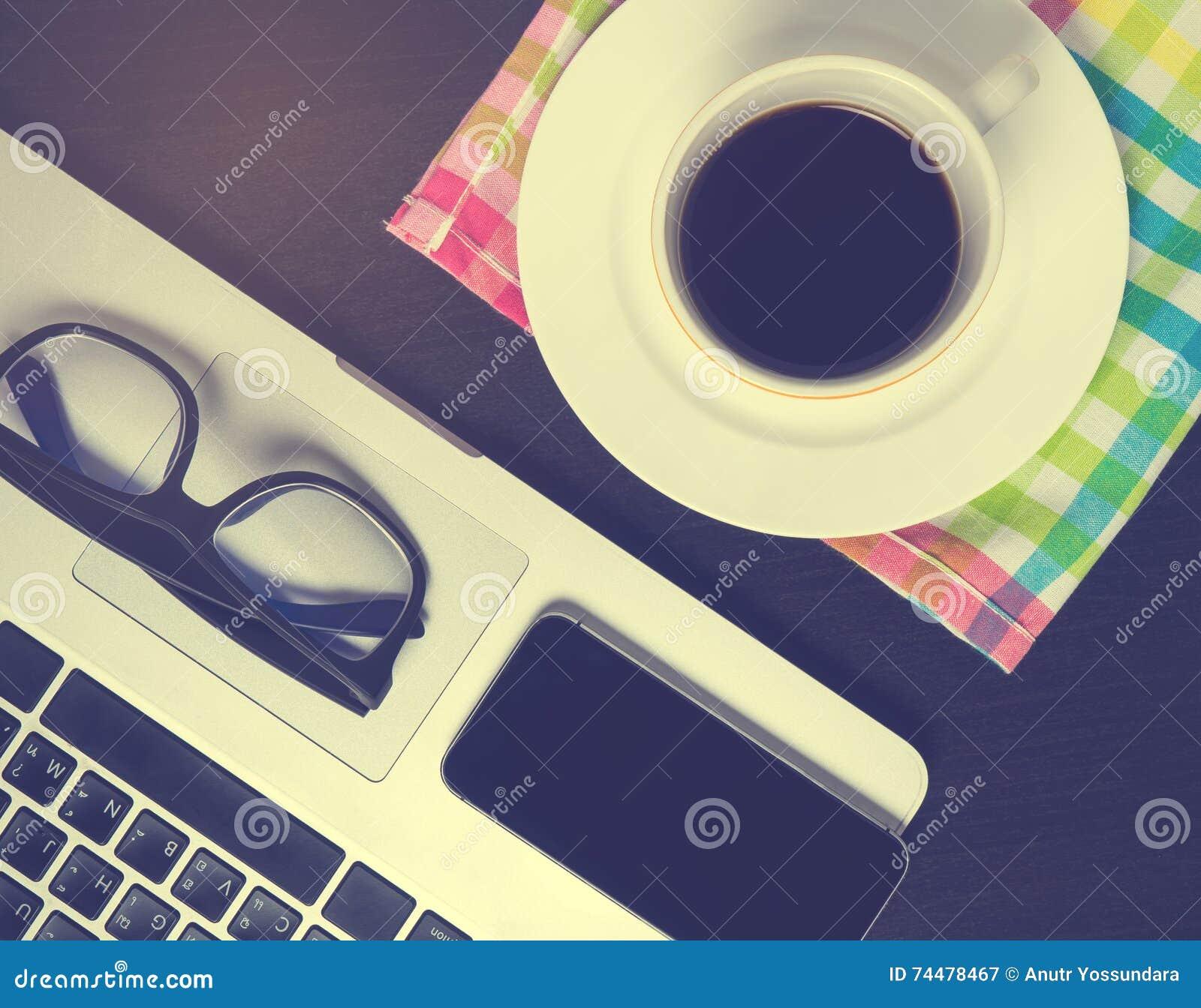 Pantalla elegante negra del teléfono en el escritorio del café de la oficina