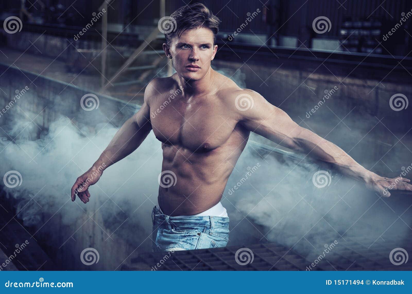 Pantalones vaqueros que desgastan del bodybuilder hermoso