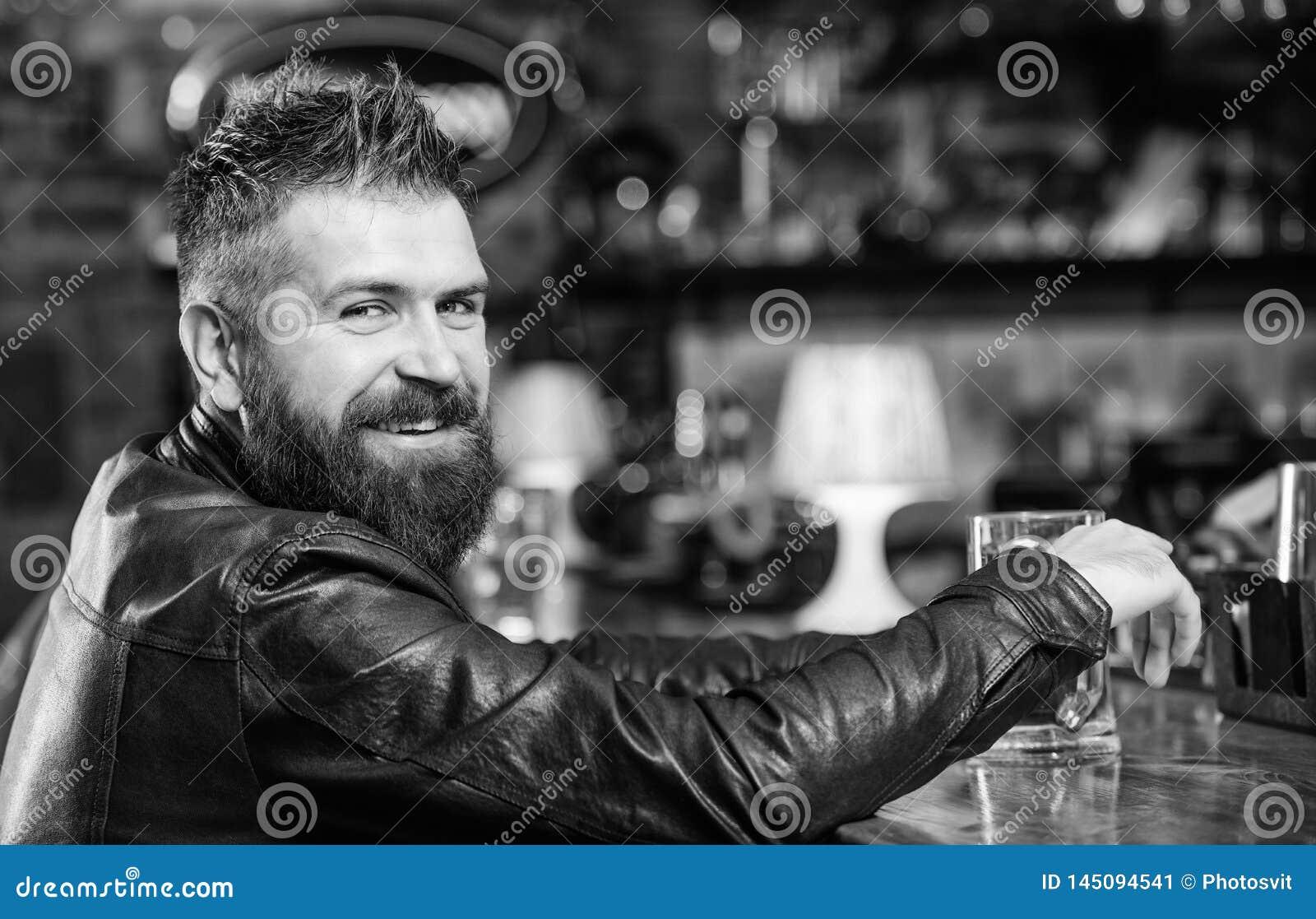 Pantaloni a vita bassa che si rilassano alla barra con birra L uomo barbuto dei pantaloni a vita bassa brutali si siede alla birr