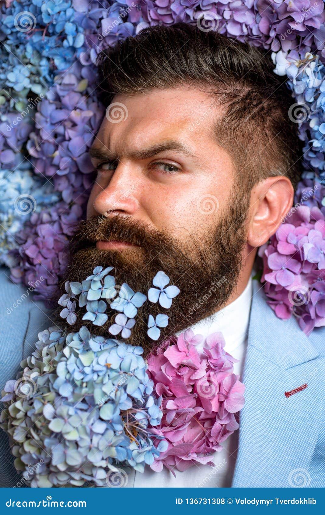 Pantaloni a vita bassa maturi con la barba Capelli e pelle sani maschio con i fiori dell ortensia Sorgente il giorno delle donne