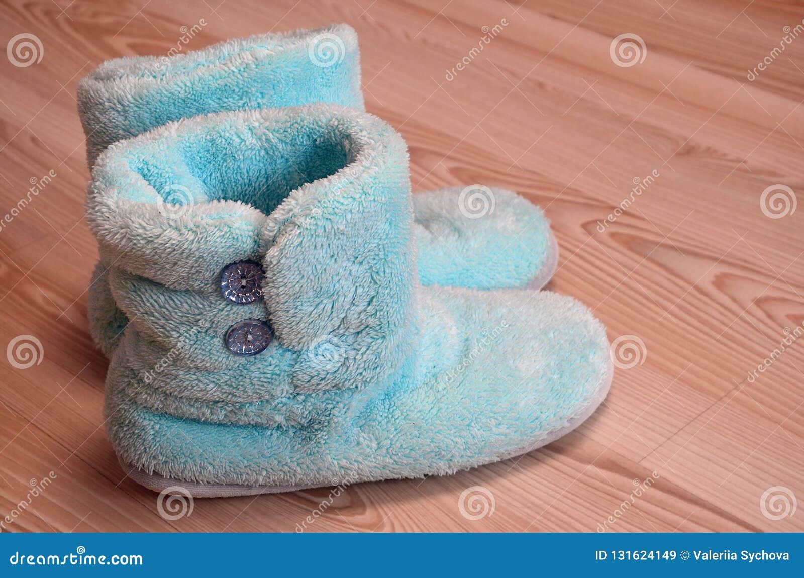 Pantofole accoglienti, calde e comode su un pavimento di parquet di legno nella stanza Spazio della copia per testo, inverno che