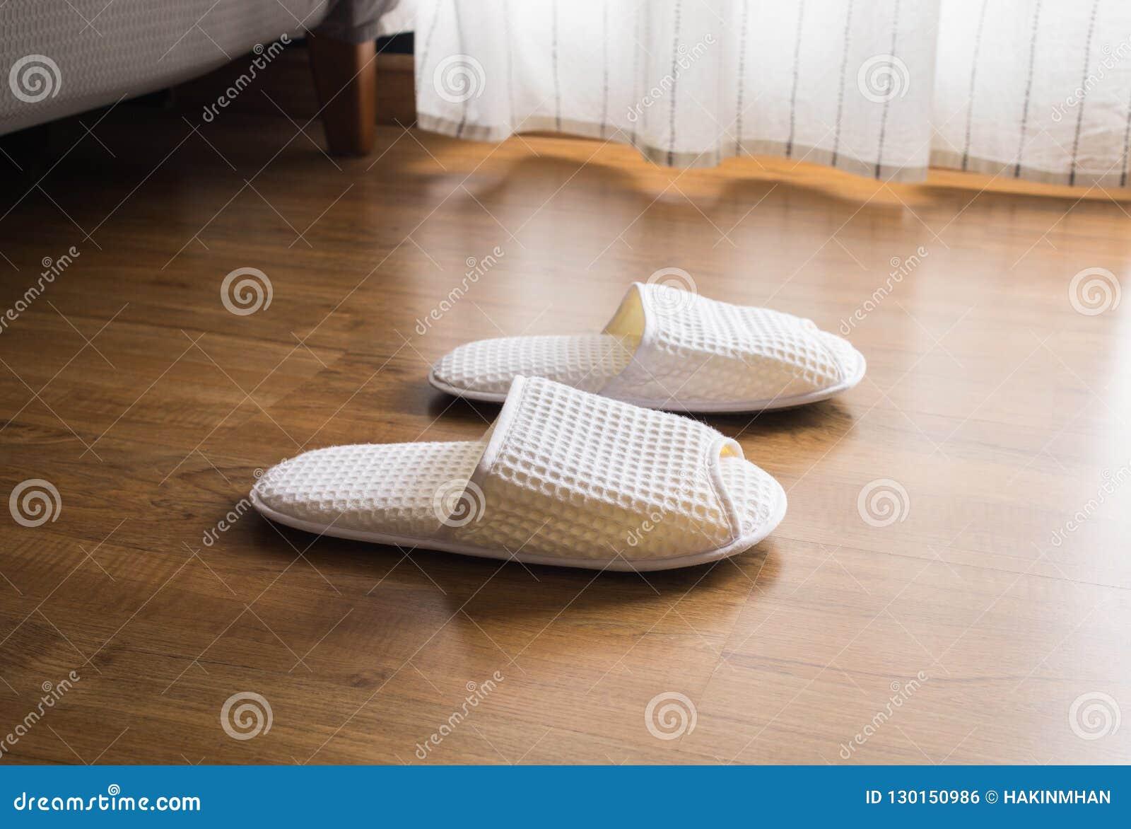 Pantoufles blanches, chaussures sur le plancher en bois dans le matin