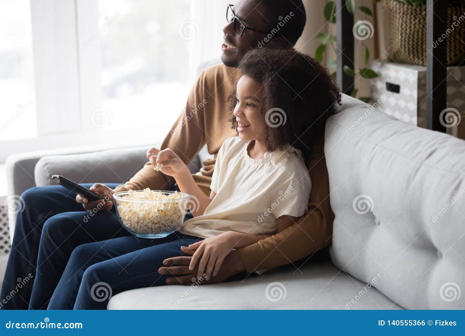 Papà africano felice della famiglia con la figlia del bambino che guarda insieme TV