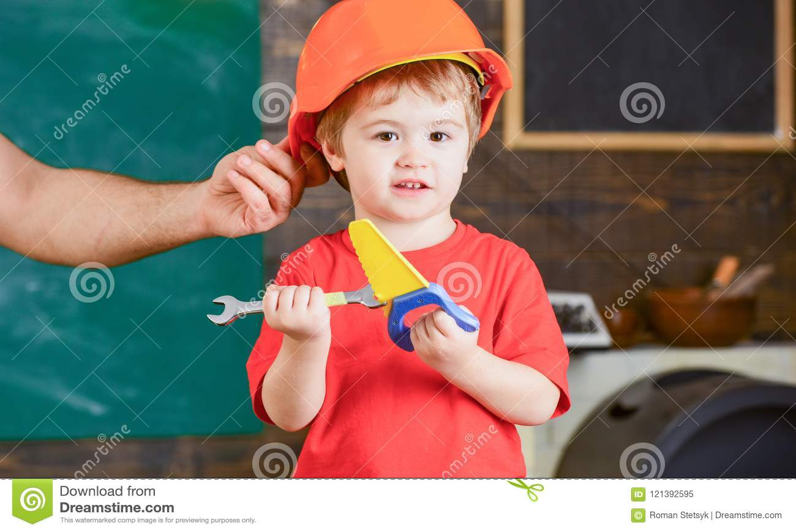 Papà d aiuto del piccolo lavoratore in officina Bambino che gioca con la sega a mano e la chiave del giocattolo Padre che tiene c