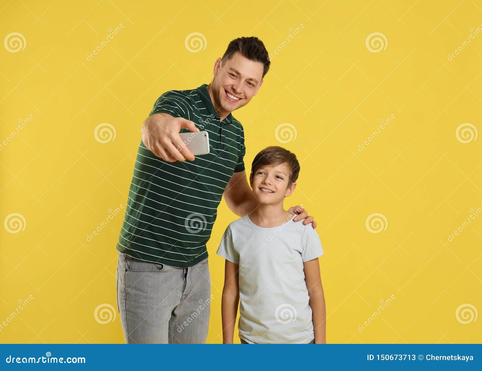 Papà ed suo figlio che prendono selfie