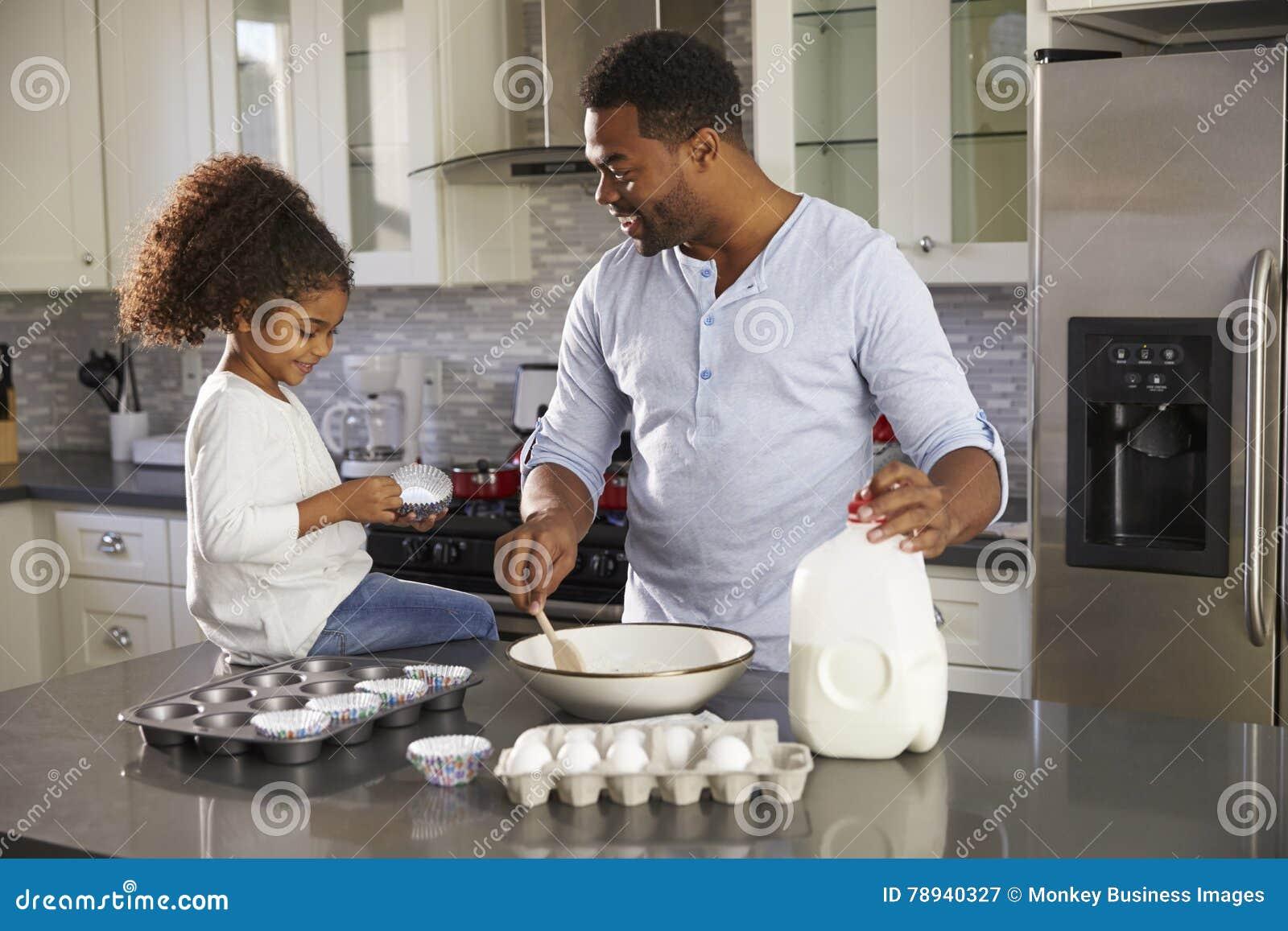 Papà nero e giovane figlia che cuociono insieme nella cucina